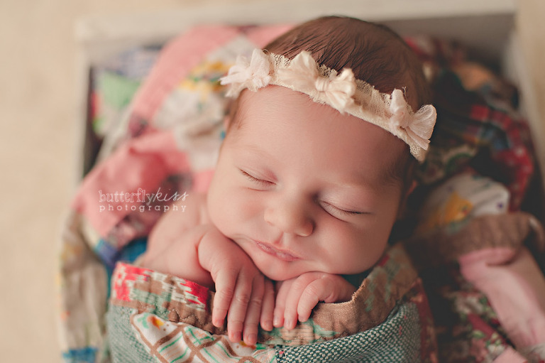 bohemian newborn baby girl with vintage pink bow headband and colorful quilt