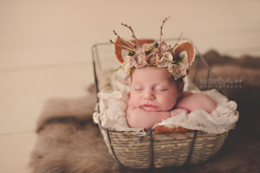 newborn baby girl with deer headband and authentic reindeer pelt, natural organic earthy colors, brown cream tan