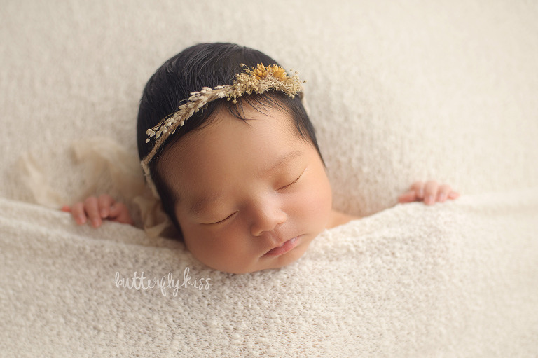 olympia newborn photographer tcked in baby pose with fingers holding blanket boho earthy natural dainty headband tieback