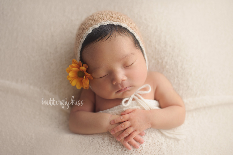 olympia newborn photographer knit bonnet neutral blush tone with real flower tucked behind ear
