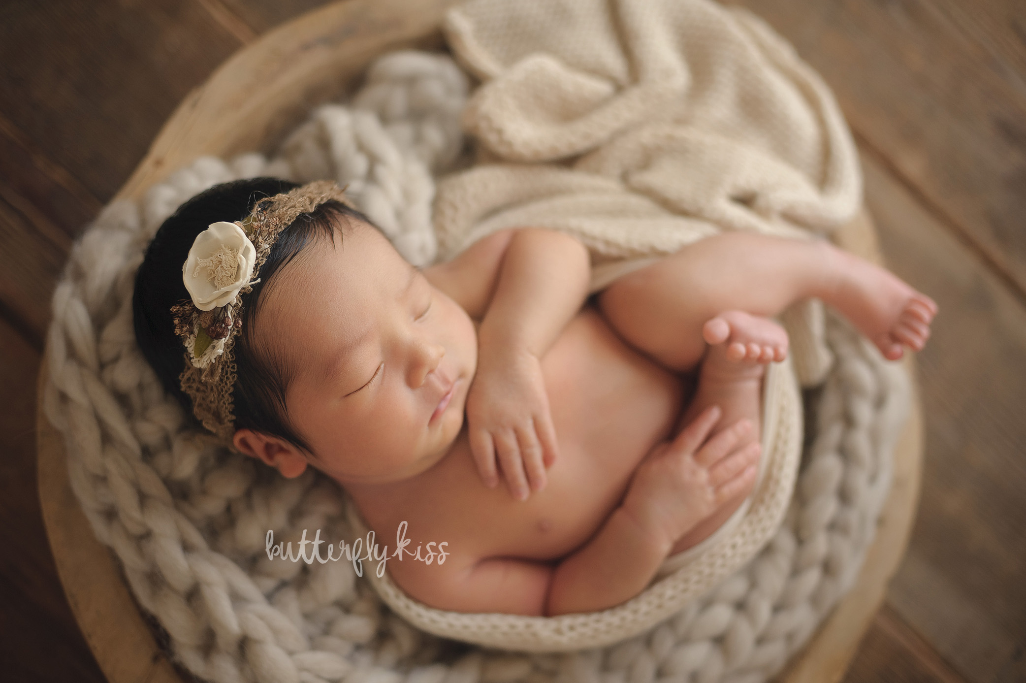 olympia newborn photographer wrapped pose inspiration in wood bwol with knit layers organic natural soft cream earth tone neutral cocoa headband tieback ethnic baby girl