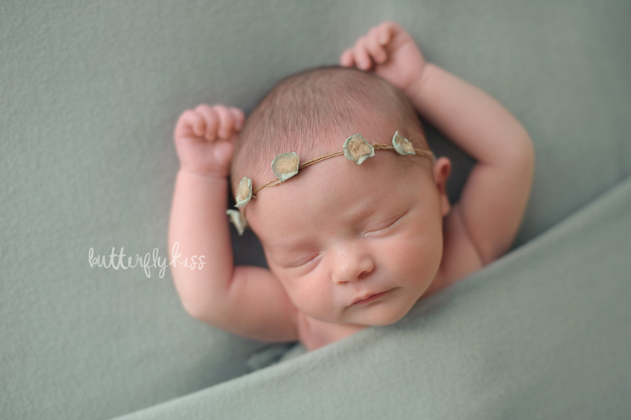 Tacoma newborn photographer Butterfly Kiss Photography baby Gwendolyn dusty mint sage robins egg blue green backdrop with dainty flower headband tucked in pose relaxed natural baby photo